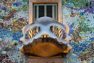 Casa Batlló facade includes, on the level of the ground floor, the Noble Floor and the first floor, slender pillars of Montjuic stone which form bone-like shapes and are decorated with typically modernist floral designs. The balcony railings in the shape of masks are made of wrought iron cast in a single piece and are secured by two anchor points in such a way that the balconies partly project outwards. As a whole, the facade is a joyful and allegorical representation, full of organic elements and colours and charged with symbolism, a wonderful spectacle in the city which inspires the most sublime sentiments in all those who gaze upon it. The house is a dialogue between light and colour.