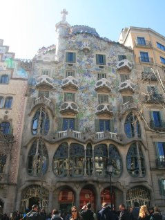 Casa Batlló, built between 1904 and 1906 in the heart of the city, is the most emblematic work of the brilliant Catalan architect.Gaudí gave Casa Batlló a facade that is original, fantastical and full of imagination. He replaced the original facade with a new composition of stone and glass. He ordered the external walls to be redesigned to give them a wavy shape, which was then plastered with lime mortar and covered with a mosaic of fragments of coloured glass and ceramic discs.At the top of the facade, the roof is in the shape of an animal's back with large iridescent scales. The spine which forms the ornamental top is composed of huge spherical pieces of masonry in colours which change as you move along the roof-tree from one end to the other.The long gallery of the main suite, the Noble Floor, overlooking Passeig de Gràcia, is composed of wooden-framed windows which are opened and closed by raising and lowering using counterweights. They are unusual in that there are no jambs or mullions, so that it is possible to raise all of the window panes and have a continuous panoramic opening running the full width of the room.