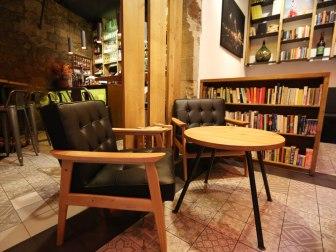 The background wall, opposite to the entrance, is dedicated to a selection of books, mostly in English and Spanish, that one can browse through while having a coffee, a vermouth, a tapa...