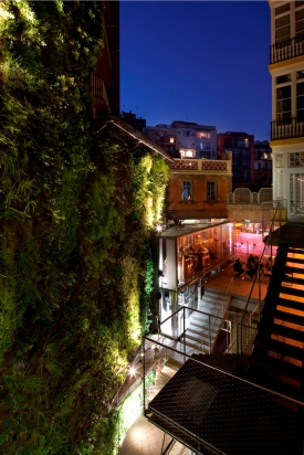 In the courtyard, the brewery's fissured brick backdrops a plant wall by Patrick Blanc—who also designed the vertical gardens of Nouvel's Musée du Quai Branly in Paris. The plant-brick combo represents a mingling of nature with industry, just like the process of making beer. Simultaneously, the plants are a living complement to the stone representations of barley and hops carved into the facade. Indeed, the project was guided overall by a desire to layer or juxtapose different eras. A clear glass wall allows the microbrewery's stainless-steel machinery, on one side, to provide a striking counterpoint to a venerable well, on the other. Now a non-operational feature of the restaurant, the well once supplied water for beer-making. The idea is revelation through contrasts, throwing each era into relief.