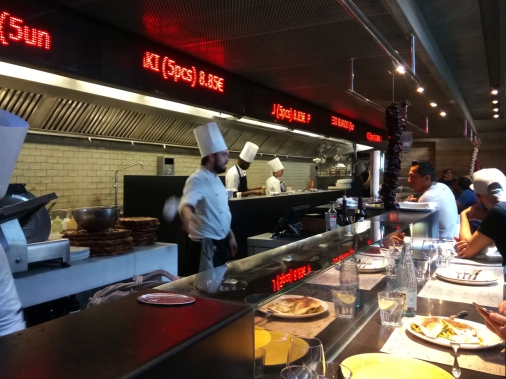 The open kitchen of Cuines de Mercat is enclosed by a food bar, the best place to have your lunch while catching all the action. Above, you might notice the names of the dishes - being displayed when they are ready to be served.