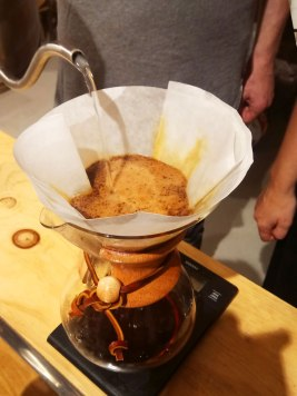 """Coffee is brewed by first placing the paper filter and the ground coffee in the neck of the flask, while heating water to 93-96 °C in a separate vessel; then """"blooming"""" (moistening) the ground coffee by pouring some hot water onto the dry coffee, and finally, by pouring the desired quantity of water (number of cups) over the ground coffee, and awaiting it to percolate down, through the coffee and the paper filter, into the flask."""