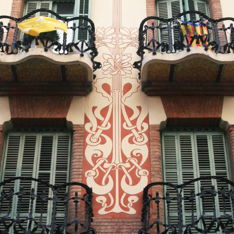 Casa Ramos red and beige sgraffito detail facade